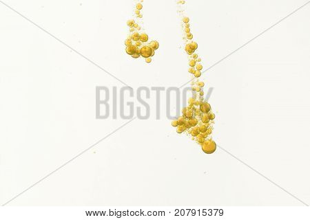 Yellow bubbles flowing over a white background.