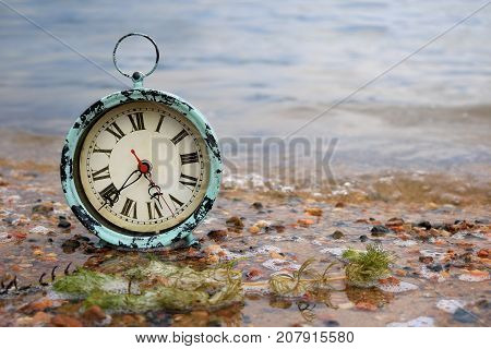 Antique alarm clock on a lakeshore in pebble covered sand