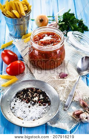 Tomato sauce and uncooked pasta on wooden background