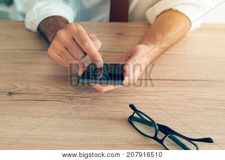 Smartphone in hands of successful businessman. Adult caucasian business person in white shirt with tucked rolled up sleeves using mobile phone at the desk in office.