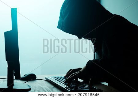 Hooded computer hacker hacking network. Male with black hoodie using computer for identity theft or other criminal online activity.