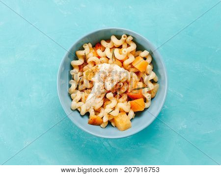 Fusilli pasta with pumpkin, rosemary and brie cheese. Idea recipe pasta. Vegetarian food. Homemade pasta dish in blue bowl over blue concrete background. Copy space. Top view or flat lay.