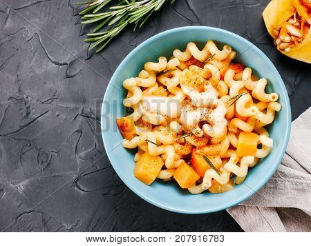 Fusilli pasta with pumpkin, rosemary and brie cheese. Idea recipe pasta. Vegetarian food. Homemade pasta dish in blue bowl over black concrete background. Copy space. Top view or flat lay.