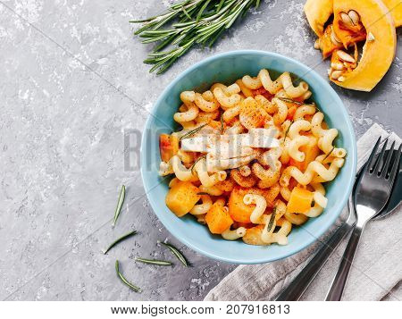 Fusilli pasta with pumpkin, rosemary and brie cheese. Idea recipe pasta. Vegetarian food. Homemade pasta dish in blue bowl over gray concrete background. Copy space. Top view or flat lay.