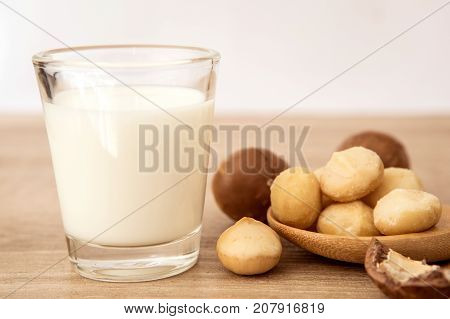 Close up the macadamia nut milk on wooden table , low fat healthy drink .