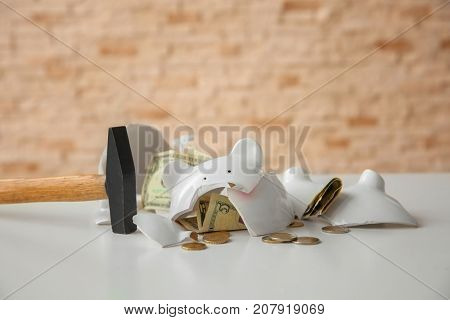 Hammer and broken piggy bank with money on table against blurred background