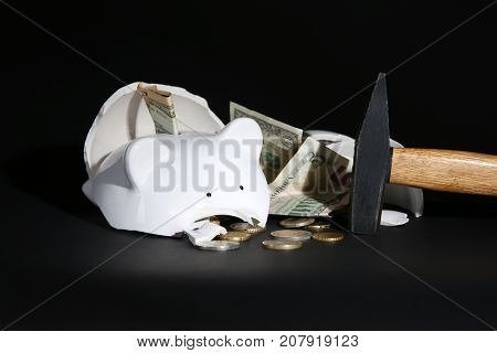 Hammer and broken piggy bank with money on black background