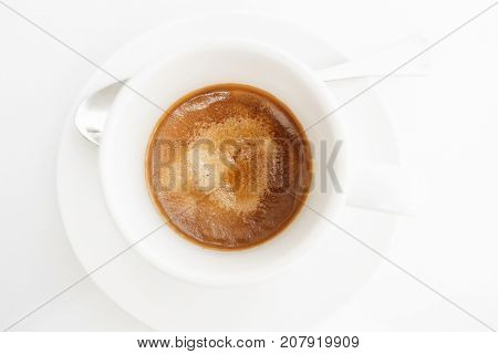 Top view of espresso coffee in white cup on white table. High key style shot.