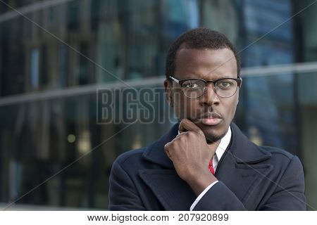 Urban Portrait Of Handsome African Businessman Dressed In Smart Coat In City Street Pressing Fist To