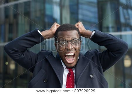 Outdoor Image Of Emotional African Male Wearing Formal Clothes And Eyeglasses Staring At Camera With