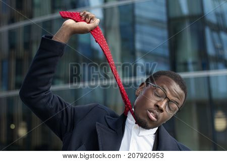 Horizontal Closeup Of Young African American Businessman Pulling Up Red Necktie As If Hanging With E