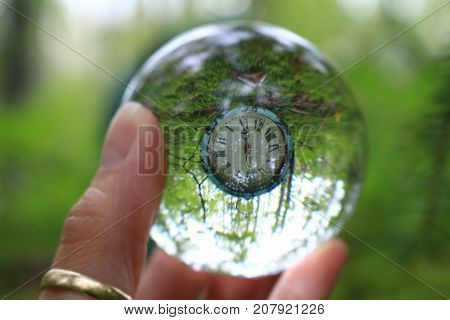 Fingers holding transparent glass ball reflecting an antique clock in the forest