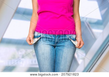 Young woman pulling out empty pockets she hasn't money