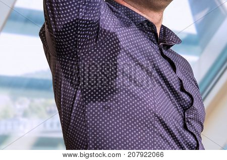 Young man with sweating under armpit in business office