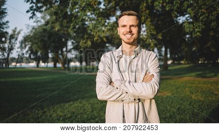 A portrait of a happy successful student standing in a park and posing to camera. His lessons are over so now he has some free time to spend outside and enjoy the warm weather and evening sunlight. The young man is smiling to the camera.