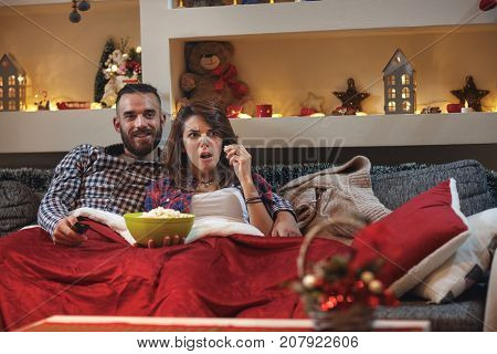 Girlfriend with boyfriend together in bad staring scared and watching tv