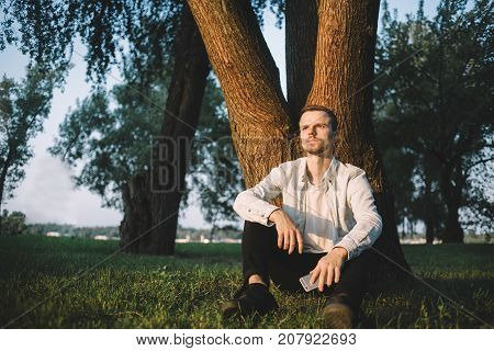 Serious and thoughtful man is sitting under the tree and thinking about something. He is holding a phone in his left hand and looking straight ahead.