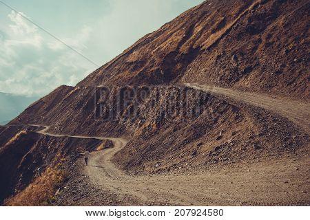 Spectacular and dangerous mountain road, Tusheti, Georgia. Adventure concept. Mount landscape. Unpaved winding road. Dirt serpentine road. Explore the world. Travel to Caucasus. Autumn. Copy space