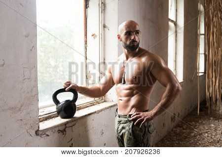 Man Exercising With Kettle Bell In Shelter