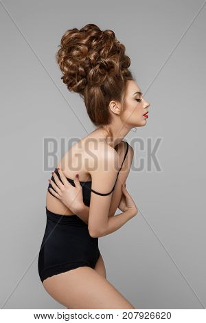 beautiful young woman in shorts and bra with high baroque hairstyle. copy space. isolated on white background.