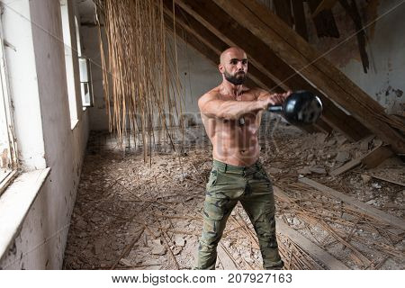 Muscular Man Exercising With Kettle-bell In Refuge