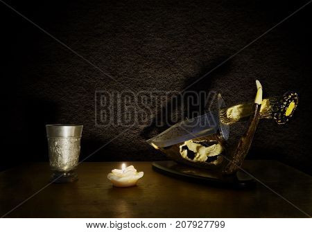 Stll life in retro style with silver wine glass, anlace and candle