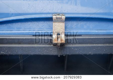 A blue dustbin with padlock with drops of water