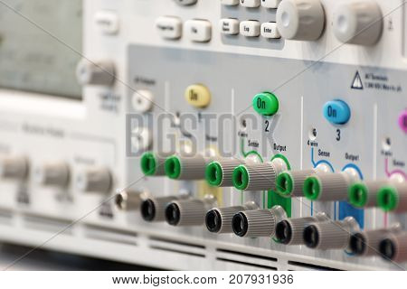 Fragment of a modern digital oscilloscope. Connector and regulator panel. Abstract industrial background.