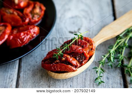 Bowl Of Sun Dried Tomatoes On Wooden Background. Sun Dried Tomatoes With Olive Oil And Herbs