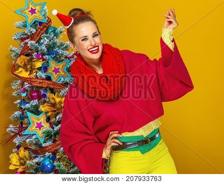 Happy Woman Near Christmas Tree Snapping With Fingers