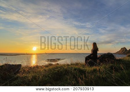 Woman sitting on a rock looking at the sunrise, at Vaeroy island, Lofoten in Norway. Sunrise.