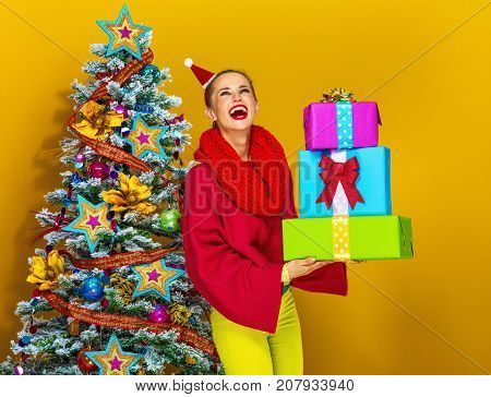 Smiling Modern Woman With Pile Of Christmas Present Boxes
