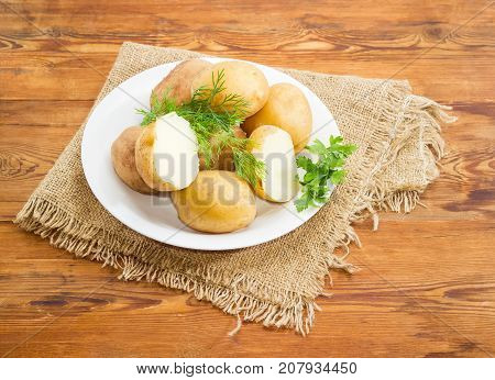Two halves and several whole potatoes boiled in their jackets decorated with twigs of parsley and dill on the white dish on a surface of old wooden planks with sackcloth