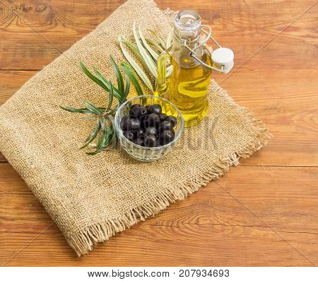 Black olives in small glass bowl glass bottle of the olive oil with open lid and olive branch on a sackcloth on an old wooden planks