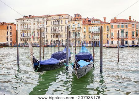 two gondolas anchored on the wooden pillars in Venice