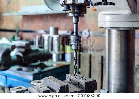 Drilling machine. The drill bit is installed in the drill chuck. Machine vice, metalworking shop. poster