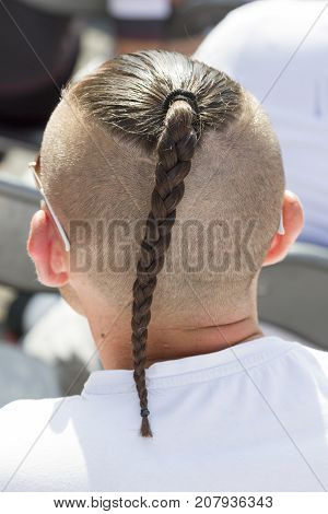 Photo from t back of man with pigtail on head