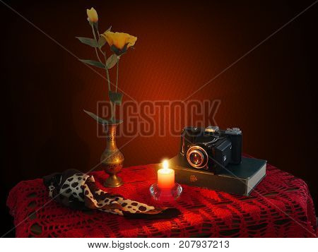 Still life with candle, book. old film camera and flowers