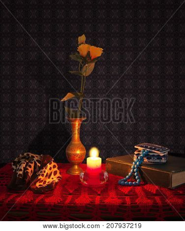 Still life with book, flowers, necklace and scarf