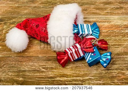 Santa's cap and colorful colored candy lay on a scratched wooden table. Close-up.