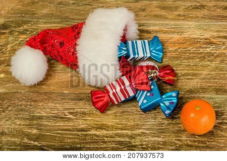 Santa's cap colorful colored candy and mandarin lay on a scratched wooden table. Close-up.