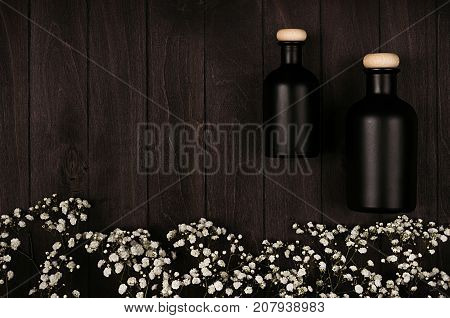 Blank black cosmetics bottles with white small flowers on dark wood board mock up top view. Template for advertising designers branding identity cover.