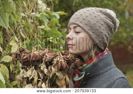 Young woman smelling a bunch of withered roses an autumn park in the blurred background