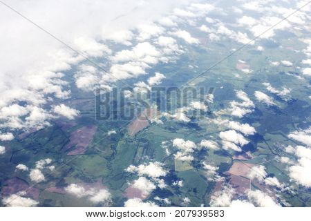 Earth through the rare clouds. View from the window of a passenger airplane.