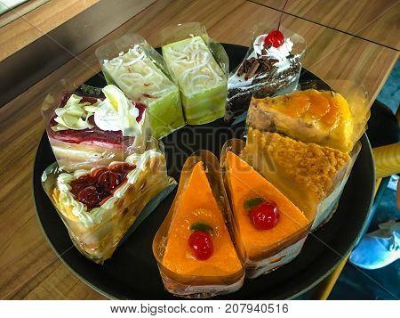 Cakes slice : chocolate cake orange cake vanilla cake fruit cake in dish on table.