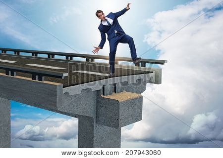 Businessman in uncertainty concept with broken bridge