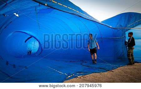 Chonburi, Thailand - December 12, 2009: Inspector walk inside the balloon to check before take off in hot air Thailand International Balloon Festival 2009