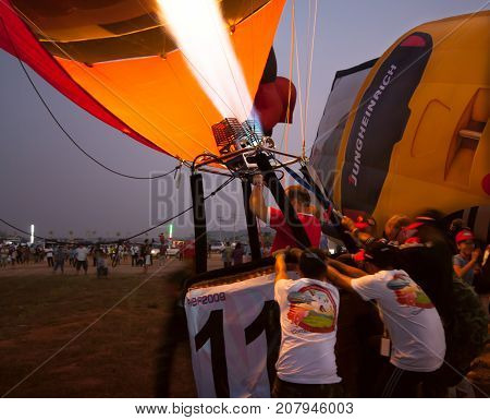 Chonburi, Thailand - December 12, 2009: Pilot heat to inflate the balloon before fly in hot air Thailand International Balloon Festival 2009