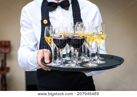 Professional waiter in black uniform serving red and white wine. Catering is serving wine and juice on a plate at business party or business event party.