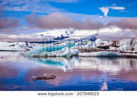 The concept of extreme northern tourism. Ice floes are reflected in the smooth water surface of Ice Lagoon